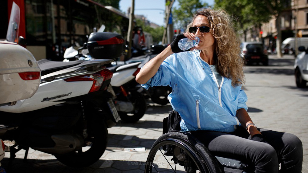 Wellspect Lofric Woman in wheelchair drinking water on sunny street
