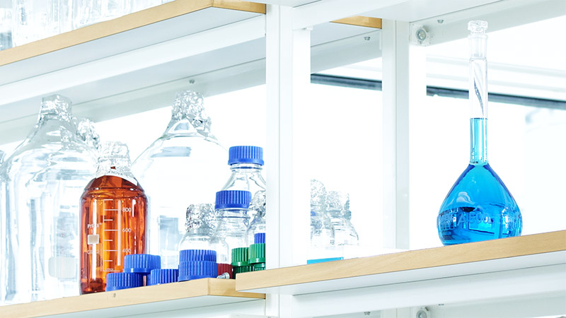 Wellspect About Laboratory shelf with bottles storing different liquids